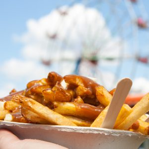 Poutine, a Canadian favorite at the fair, where junk food reigns supreme, held up in front of the ferris wheel